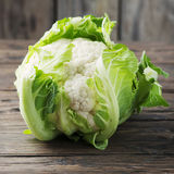 Fresh raw cauliflower on the wooden table. Selective focus and square image Stock Image