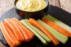 Fresh raw celery and carrots  and cheese cream sauce dip close-u Stock Photo