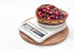 FRESH RAW CHERRIES WOODEN BASKET DIGITAL SCALE.  Royalty Free Stock Photos