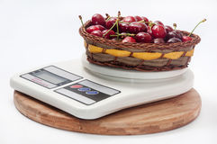 FRESH RAW CHERRIES WOODEN BASKET DIGITAL SCALE.  Stock Photos