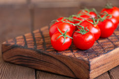 Fresh raw cherry tomatoes on a wooden board with pepper garlic. Wooden background. Close up and copy space Stock Photography