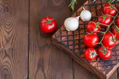 Fresh raw cherry tomatoes on a wooden board with pepper garlic. Wooden background. Close up and copy space. Overhead view Royalty Free Stock Photo
