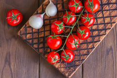Fresh raw cherry tomatoes on a wooden board with pepper garlic. Wooden background. Close up and copy space. Overhead view Royalty Free Stock Image