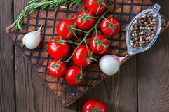 Fresh raw cherry tomatoes on a wooden board with pepper garlic a. Nd rosemary bunch. Close up and copy space. Top view Royalty Free Stock Image