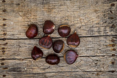 Fresh raw chestnuts. On a wooden background Royalty Free Stock Photography