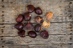 Fresh raw chestnuts. On a wooden background Stock Images