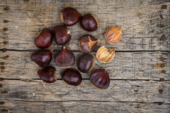 Fresh raw chestnuts. On a wooden background Stock Image