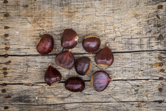 Fresh raw chestnuts. On a wooden background Stock Photography