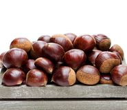 Fresh  raw chestnuts in a wooden box isolated on white backgroun. D Royalty Free Stock Images
