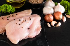 Fresh raw chicken breast fillet. With ingredient on black background Stock Photo