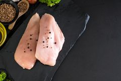 Fresh raw chicken breast fillet. With ingredient on black background Royalty Free Stock Photo