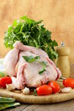 Fresh raw chicken on a cutting board with vegetables. And herbs Stock Photography
