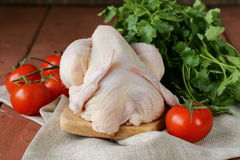 Fresh raw chicken on a cutting board with vegetables. And herbs Stock Photos