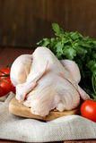 Fresh raw chicken on a cutting board with vegetables. And herbs Stock Photo