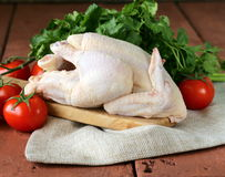 Fresh raw chicken on a cutting board with vegetables Royalty Free Stock Photos