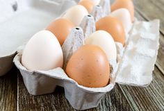 Fresh raw chicken eggs in carton egg box on wooden background. Close-up view on brown and white eggs. The main ingredient for many dishes Stock Photos