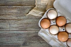 Fresh raw chicken eggs in carton egg box on wooden background. The top view on brown and white eggs. Close-up view. The main ingredient for many dishes. Free Royalty Free Stock Image