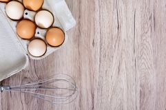 Fresh raw chicken eggs in carton egg box on wooden background. The top view on brown and white eggs. Close-up view. The main ingredient for many dishes. Free Stock Photography