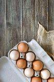 Fresh raw chicken eggs in carton egg box on wooden background. The top view on brown and white eggs. Close-up view. The main ingredient for many dishes. Free Stock Images