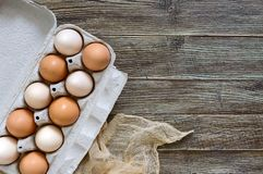 Fresh raw chicken eggs in carton egg box on wooden background. The top view on brown and white eggs. Close-up view. The main ingredient for many dishes. Free Royalty Free Stock Images