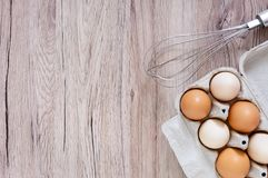 Fresh raw chicken eggs in carton egg box on wooden background. The top view on brown and white eggs. Close-up view. The main ingredient for many dishes. Free Royalty Free Stock Photography