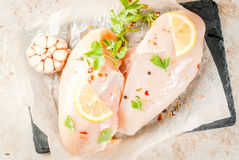 Fresh raw chicken fillet, breast. Fresh raw unprepared chicken fillet, breast. With spices, herbs, garlic and lemon for cooking. On a light stone table. Top view Royalty Free Stock Photo