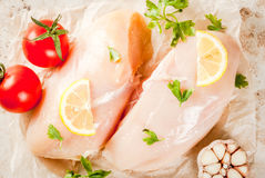 Fresh raw chicken fillet, breast. Fresh raw unprepared chicken fillet, breast. With spices, herbs, tomatoes, garlic and lemon for cooking. On a light stone table Royalty Free Stock Photos