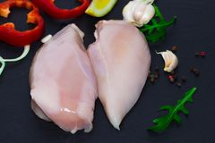 Fresh raw chicken fillet, spices, herbs and vegetables on black. Background, top view Royalty Free Stock Photo