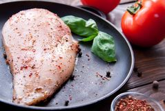 Fresh raw chicken fillet sprinkled with herbs and spices and a basil leaf on a black frying pan on a wooden table with. Red tomatoes and pepper in a container Stock Photo