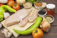 Fresh raw chicken fillet and vegetables prepared for cooking. Fresh raw chicken breasts. Stock Photos
