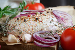 Fresh raw chicken with herbs, garlic, onion, tomatoes and chilli. Pepper. Close up Royalty Free Stock Photo