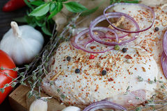 Fresh raw chicken with herbs, garlic, onion, tomatoes and chilli. Pepper. Close up Stock Photography