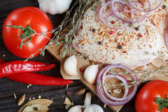 Fresh raw chicken with herbs, garlic, onion, tomatoes and chilli. Pepper. Close up Stock Image