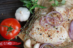 Fresh raw chicken with herbs, garlic, onion, tomatoes and chilli Stock Images
