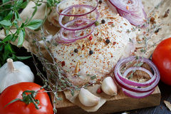 Fresh raw chicken with herbs, garlic, onion, tomatoes and chilli. Pepper. Close up Stock Photo