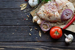 Fresh raw chicken with herbs, garlic, onion, tomatoes and chilli. Pepper on dark wooden background Stock Photography