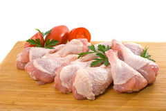 Fresh Raw Chicken Legs. Fresh raw chicken wings on chopping board with roma tomatoes Royalty Free Stock Photography
