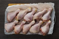 Fresh raw chicken legs arrangement on kitchen cutting board. Fresh raw chicken legs arrangement on a kitchen cutting board Royalty Free Stock Image