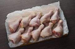 Fresh raw chicken legs arrangement on kitchen cutting board. Fresh raw chicken legs arrangement on a kitchen cutting board Stock Images