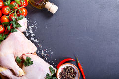 Fresh raw chicken. Legs with vegetables on dark background Stock Photo