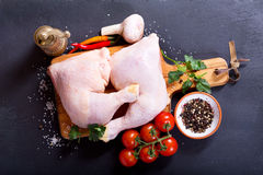 Fresh raw chicken legs with vegetables. On dark background Stock Photography
