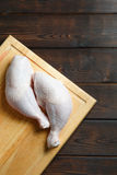 Fresh raw chicken legs on wooden board. On the wooden background Stock Photo