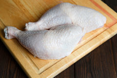 Fresh raw chicken legs on wooden board Royalty Free Stock Image
