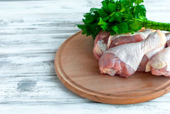 Fresh raw chicken legs on wooden board. Raw chicken legs on a wooden Board with fresh parsley Stock Images