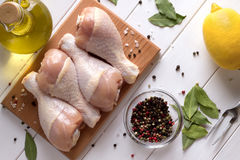 Fresh raw chicken meat on cutting board with spices. Top view. Fresh raw chicken meat on cutting board with spices, oil and lemon. Top view Stock Photos