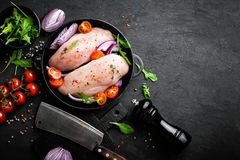 Fresh raw chicken meat, fillet marinated with spices, onion and tomatoes on black background. Top view Stock Image