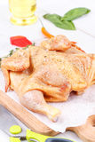 Fresh raw chicken prepared for roast with thyme and tomatoes. Cherry Stock Photos