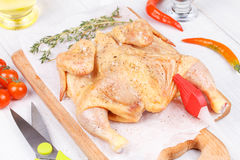 Fresh raw chicken prepared for roast with thyme and tomatoes. Cherry Stock Photography