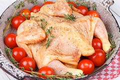 Fresh raw chicken prepared for roast with thyme and tomatoes. Cherry Stock Image
