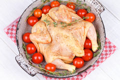 Fresh raw chicken prepared for roast with thyme and tomatoes. Cherry Stock Photo